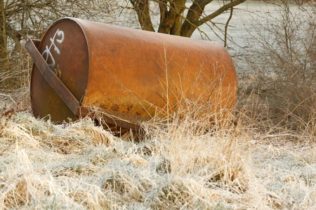 forgotten: This photo shows forgotten old corroded road roller in the frozen grass and surrounded by trees. This photo was taken early in the winter morning.
