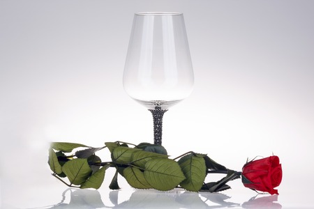 shadowed: This photo shows close-up of wine glass with red rose on the shadowed background. Stock Photo