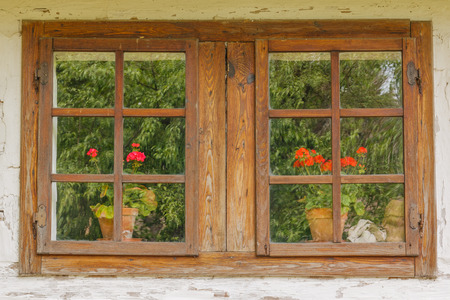 This photo shows a closeup of old wooden windows with flowers. Foto de archivo