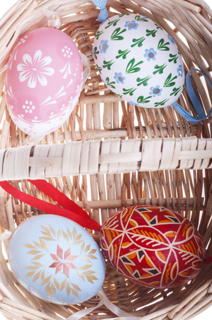 topdown: Photo shows top-down close-up of isolated strawy basket and Easter eggs. Stock Photo