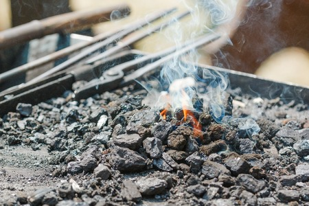 fire place: Photo shows close-up of metal fire place with flames during a day. Stock Photo