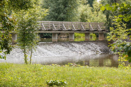 floating bridge: Photo shows old wooden bridge above floating river in summer.