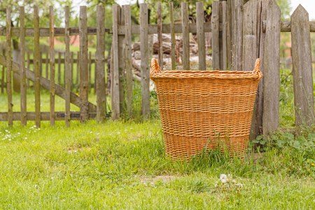 window graffiti: This photo shows a detail of old wooden basket in front of fence in the village.