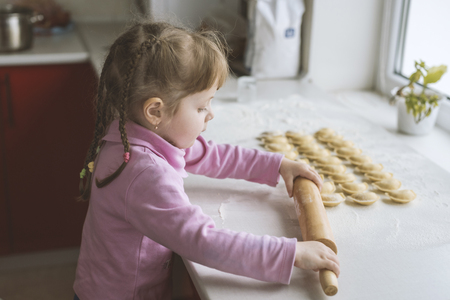 The little girl is trying to roll out the dough, concentration. Ukraine