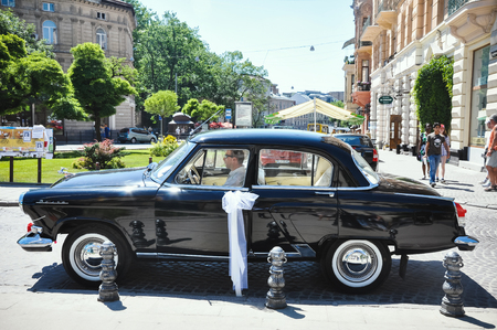 Lviv, Ukraine - June 5, 2011: Soviet car 60-xx years Volga GAZ-21. The driver expects young couple is crowned in the church. Editöryel