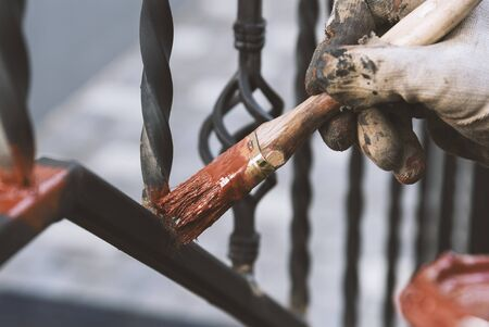 Painting forged railings on the stairs at the entrance of the house. Protection against rust. Working processes.
