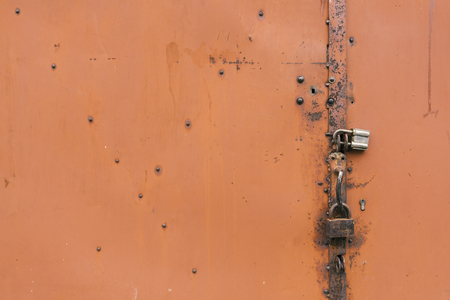 Detail of the painted metal door with old padlocks, closeup