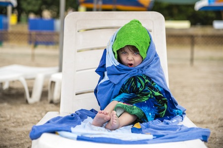 The little girl wrapped in towels for warming, emotions of the face Stock Photo