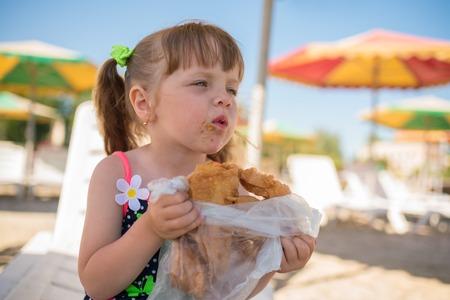 baklava: The little girl eats baklava, dirty face, summer vacation