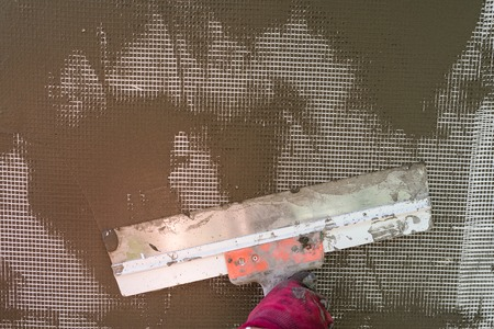 Plastering the wall with a spatula, working process, close-up Stock Photo