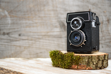 Old vintage camera on wooden stand, wooden background, retro theme, hobbies and auctions
