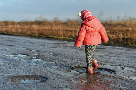 Little girl plays in puddle, dirty and wet shoes, childrens fun, unforgettable moments, fun with father, life in village, sunlight. Concept - little roister. Imagens