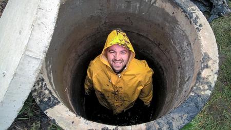 Man is inside sewage pit, sewage works, work near home, men at work