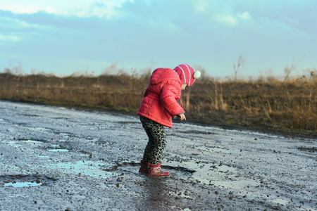 Concept - happy childhood. Little girl plays in puddle, children's fun, unforgettable moments, dirty and wet shoes, fun with father, village life Banque d'images