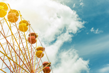 Ferris wheel with blue cloudy sky on background, summer vacation theme, copy space