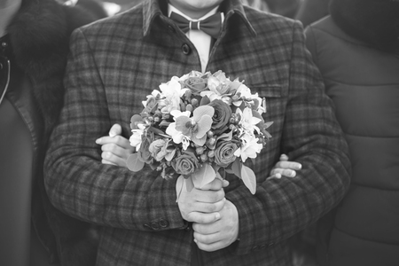 Groom in stylish clothes with bouquet in his hands is going to bride, wedding day, black and white toning