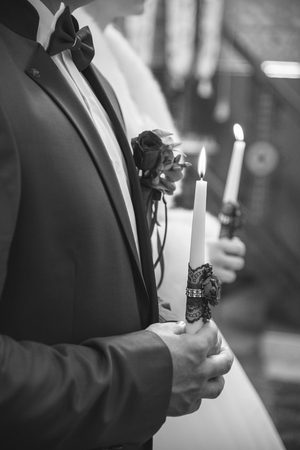 Wedding ceremony in church, young married couple holding candles, christian traditions Reklamní fotografie