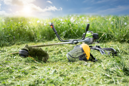 String trimmer and protective face mask on mown grass, growing grass and the blue sky on the background, sunlight