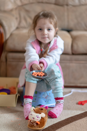 Little four years old girl sitting on potty and play with kinetic sand, toys and slippers scattered around. Carefree childhood Stock Photo