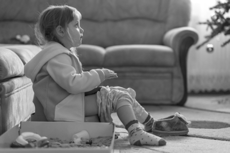 Little four years old girl sitting on potty, playing with kinetic sand and watching TV, monochrome effect
