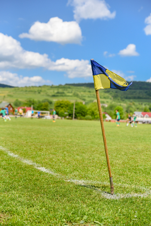 Amateur soccer field, retro corner flag on the foreground, football players are fighting for the ball on the background. Stories about rural life in Ukraine