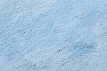 Aged adobe whitewashed wall in light-blue color, retro background, detailed texture
