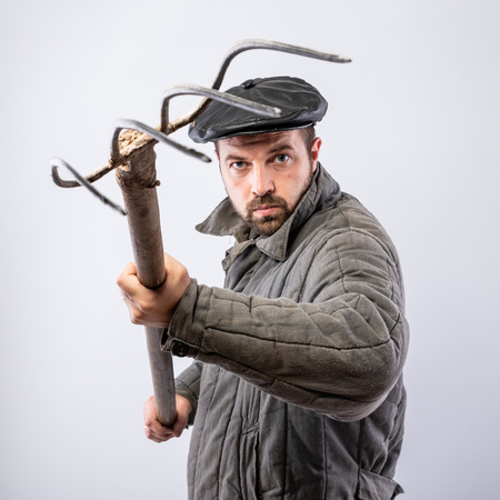 Conception - angry farmer. Bearded man in old-fashioned clothes with pitchfork in hand, danger