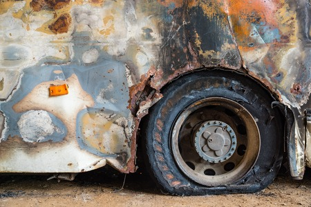 Burned down bus, view from outside, damaged walls and flat tire Reklamní fotografie