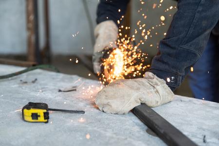 Processo di taglio del profilo metallico con smerigliatrice angolare elettrica. Preparazione di parti per la saldatura di costruzioni metalliche. Persone al lavoro, professione e abilità Archivio Fotografico