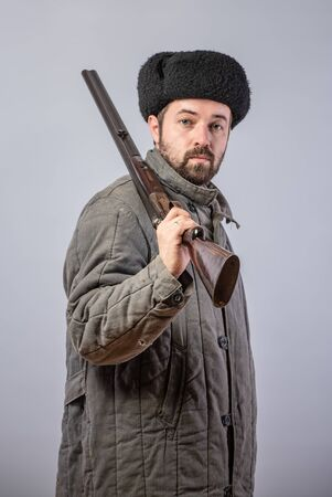 Peasant with a rifle on his shoulder, old-fashioned clothes, retro theme, studio shot