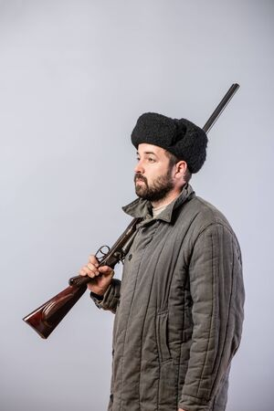Hunter with a rifle on his shoulder, old-fashioned clothes, retro theme, studio shot Фото со стока