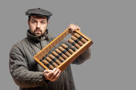 Old fashioned bearded man with wooden retro abacus, studio shot. Isolated on gray background, with clipping path 写真素材