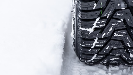 Reliable winter tires - safety of passengers. Wheel in the snow, close up. 版權商用圖片