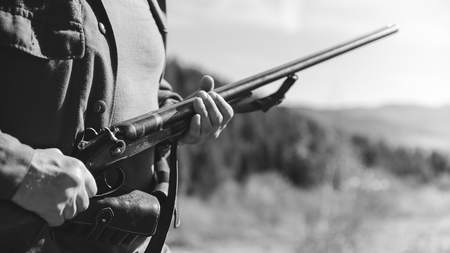 Hunter with horizontal double-barreled shotgun on hunting in the mountains