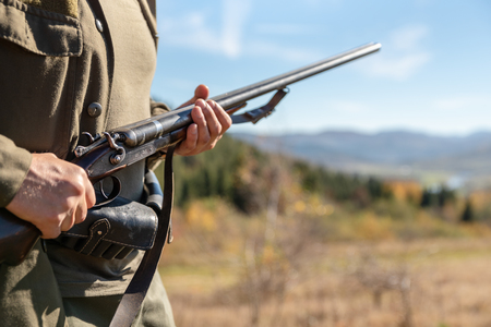 Guard on the environment at work, horizontal double-barreled shotgun in the hands, in the mountains. Stockfoto