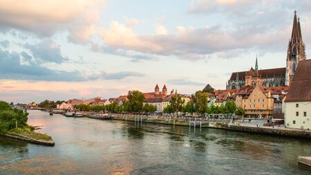 Regensburg, Germany - 26 July, 2018: Medieval architecture of Old Town of Regensburg city. Tourist ships on the Danube river. Regensburg Cathedral in the background. Popular tourist places Editorial