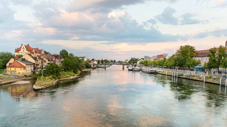 Regensburg, Germany - 26 July, 2018: Beautiful sunset on Danube river. Tourist ships on the water. Medieval architecture of Old Town of Regensburg.