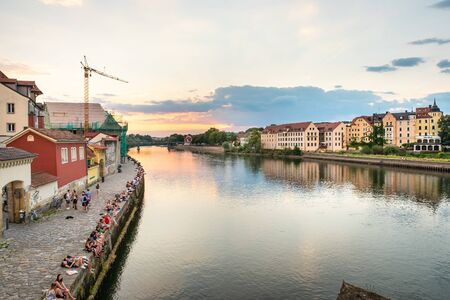 Regensburg, Germany - 26 July, 2018: People have rest on Danube River bank. Beautiful sunset. Popular tourist destinations in Regensburg. Editorial