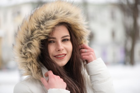 Portrait of young beautiful girl, warm and comfortable winter clothes, outdoors, winter time. 版權商用圖片