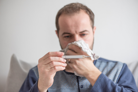 ill man checks the body temperature with a mercury thermometer. Theme of viral diseases, flu, colds.