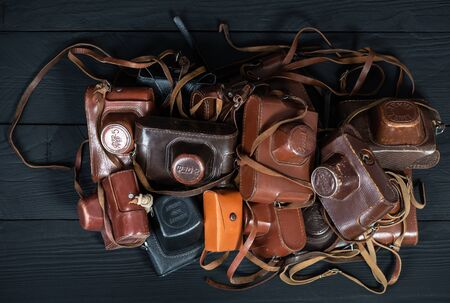 Drohobych, Ukraine - 02 February, 2019: Heap of 35mm retro cameras in leather covers on black, top view Editorial
