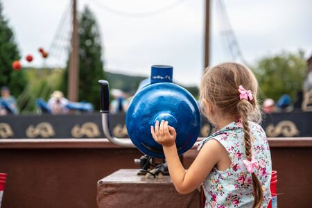 Loifling, Germany - 26 July, 2018: Little girl plays near toy cannon on Pirates of Caribbean attraction in Churpfalzpark Loifling. Rest and fun for everyone