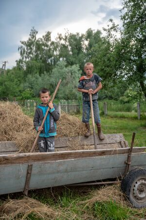 Litynia village, Ukraine - June 02, 2018: Two little boys on retro cart. Work near hay for livestock. Life in a village Editorial