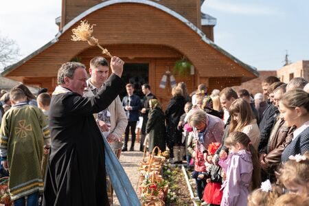 Voroblevychi village, Drohobych district, Western Ukraine - April 07, 2018: Priest consecrates Easter baskets with sacred water. Traditions of celebration of Easter in Ukraine