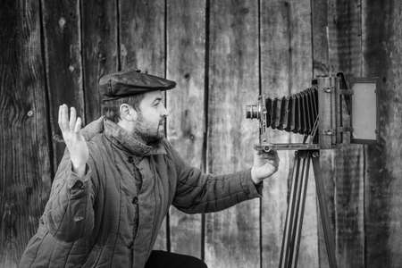 Selfie of old fashioned man on large format camera. Idea- selfie Фото со стока
