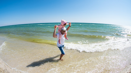 Father with a little daughter are having fun on the sandy beach of Black sea. Summer vacation, Dzharylhach island, Ukraine Stock Photo