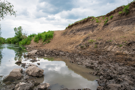 Watering place, traces of hoofs of cows and horses in the valley of river. Grazing livestock. Life in village, Ukraine