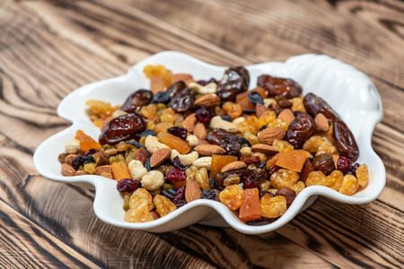 Plate of dried fruits on wooden table, Mix of nuts and berries: cashews, hazelnut, almonds, yellow, brown and blue raisins raisins, cranberries, dried dates and apricots Stock Photo