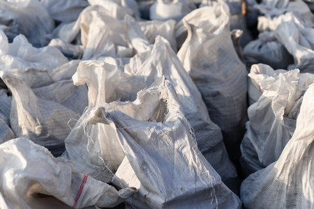 Group of filled plastic woven sacks, packing of goods for transportation and storage in a warehouse, polypropylene bags.