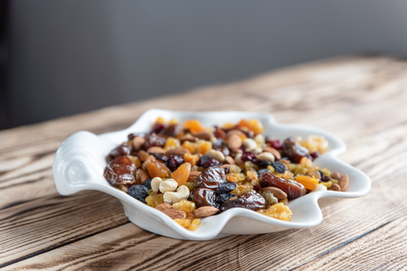 Plate of dried fruits on wooden table, Mix of nuts and berries: raisins, hazelnut, cashews, almonds, cranberries, dried dates and apricots. Stock Photo